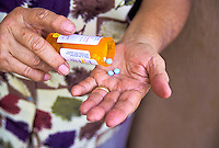 An elderly part-Hawaiian woman empties pills from a prescription container into her hand.