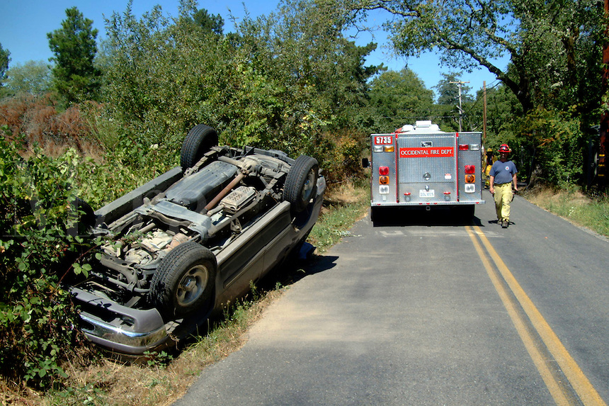 Firefighters arrive at the scene of a single vehicle accident in Occidental California.  The car slid and rolled upside down.