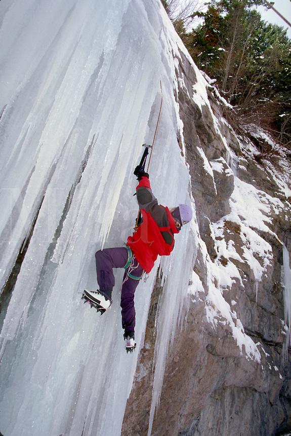 Woman ice climbing in the Rocky Mountains, CO., Colorado.