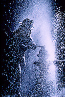 A firefighter struggles with a fire hydrant as it sprays during a firefighting operation.