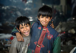 Almir Dasi (left), 6, and his brother Armando, 8, lived under a bridge in a Roma settlement in Belgrade, Serbia, when this photo was taken in February 2012. Their parents were refugees from Kosovo. The families that lived here, most of whom survive from recycling cardboard and other materials, were forcibly evicted in April 2012. Many were moved into metal shipping containers on the edge of Belgrade..