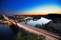 Cars lights streak past the Austin 360 Bridge during a saturated Sunset on Lake Austin