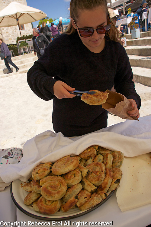 Alacati, Turkey: the Ot Festivali or Herb Festival held in spring every year. Stallholder with a pastry (el acmasi borek) stuffed with herbs and greens