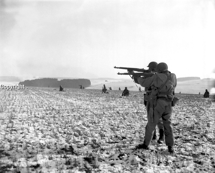 Infantrymen, attached to the 4th Armored Division, fire at German troops, in the American advance to relieve the pressure on surrounded airborne troops in Bastogne, Belgium.  December 27, 1944.  Pfc. Donald R. Ornitz.  (Army)<br /> NARA FILE #:  111-SC-199295<br /> WAR & CONFLICT BOOK #:  1074