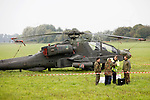 """Foto: VidiPhoto<br /> <br /> ELBURG - Het Downed Aircraft Recovery Team (DART) van de Luchtmacht probeert donderdag met man en macht het Apachetoestel te repareren dat woensdagavond een voorzorgslanding moest maken in een weiland bij Elburg. Na reparatie kan het dan weer terugkeren naar vliegbasis Gilze-Rijen. Mocht reparatie niet lukken, dan wordt het gevechtstoestel via de weg getransporteerd. De helicopter trekt veel aandacht van het publiek. Het terrein rond de Apache is afgezet met linten en wordt bewaakt door Defensiepersoneel. De tweekoppige bemanning besloot rond 21.00 uur woensdagavond om te landen omdat de technische systemen aan boord aangaven dat er mogelijk iets aan de hand was, aldus een woordvoerder van de luchtmacht. """"Om veiligheidsissues te voorkomen, wordt de helikopter dan uit voorzorg aan de grond gezet. Het was alleen even kijken waar dat veilig kon."""""""