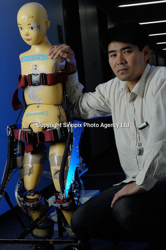 """Dr Hiroshi Kobayashi poses next to the """"Active Walker""""   at the Department of Mechanical Engineering, Tokyo University of Science. The Active Walker is a suit that will enable children who are disabled and unable to use leg muscles to walk."""