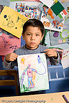 Education Preschool 4-5 year olds art activity serious boy holding up drawing he did with marker recognizable human figure vertical