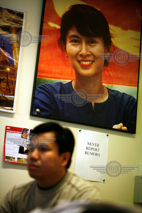 """Behind journalist Htet Aung Kyan is a portrait of Aung San Suu Kyi, above note saying """"NEVER REPORT RUMORS"""".  Democratic Voice of Burma is radio and TV station run by exiled Burmese. Opposing the government, the DVB has been transmitting, from the Norwegian capitol Oslo, into Burma since 1992."""