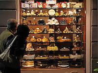 Couple looking in window at desserts in bakery window in Assisi, Ital