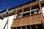 Cusco, Peru. Typical carved wooden balcony with the Cusco rainbow flag.