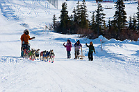School girls walk down the road and welcome Bill Pinkham into the Elim checkpoint during the 2010 Iditarod