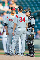 Carolina Mudcats pitching coach Jeff Harris (34) has a chat on the mound with pitcher Joseph Colon (29) and catcher Tony Wolters (11) during the Carolina League game against the Winston-Salem Dash at BB&T Ballpark on July 25, 2013 in Winston-Salem, North Carolina.  The Mudcats defeated the Dash 5-4.  (Brian Westerholt/Four Seam Images)