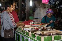 Bali, Indonesia.  Jimbaran Fish Market.  Woman Calculating Price of Fish for Two Buyers.