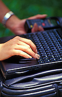 Closeup of a woman's hands typing on a black laptop computer.