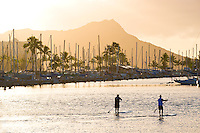 Two paddle boarders in the Ala Wai Boat Harbor in the early morning with Diamond Head in the background.
