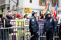 "Police presence is heavy as hundreds of protesters march early in the morning on November 17, 2011 in New York City with the aim to shut down Wall Street and the Stock Exchange.  The action was the first in a day of protests celebrating the two month anniversary of the ""Occupy Wall Street"" movement.  While many workers were inconvenienced by the human (and police) barricades, the Stock Exchange opened on schedule."