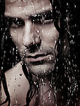 Man face with water running down it and wet long hair, artistic portrait Image © MaximImages, License at https://www.maximimages.com