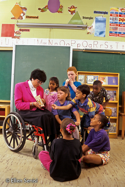 MR / Schenectady, NY.Howe International Magnet School / Grade 1 .Disabled teacher with paraplegia reads book to small group..MR: ST9603.PN#: 17765                  FC#: 27379-00319.scan from slide.©Ellen B. Senisi