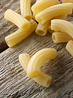 Traditional dried  Italaian Maccheroni di Toscana pasta close up in a rustic setting on wood