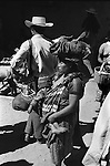 Chimaltenango Guatemala Central America. 1973. Indigenous Indian women at market carrying child and chicken on her head.