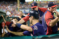 Minnesota Twins catcher Joe Mauer #7 is greeted in the dugout by his temamates after scoring a ninth inning run in the Major League Baseball game against the Texas Rangers at the Rangers Ballpark in Arlington, Texas on July 27, 2011. Minnesota defeated Texas 7-2.  (Andrew Woolley/Four Seam Images)