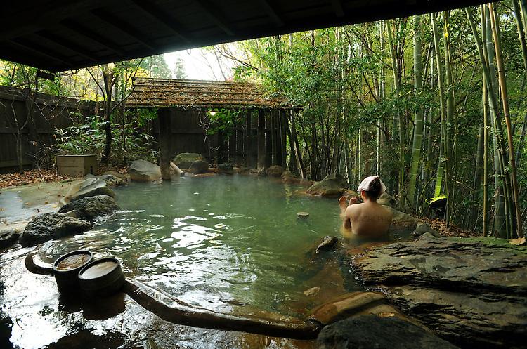 A Japanese woman takes a bath in Robenburo, outdoor bath, surrounded by bomboo in Kurokawa onsen hot spring.<br /> <br /> Une femme japonaise prend un bain à Robenburo, bain en plein air, entourée de bomboo dans la source thermale de Kurokawa onsen. Japon.