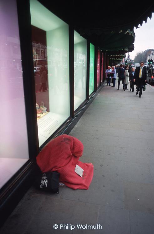 A homeless man begs outside the luxury Harrods store in Knightsbridge, central London