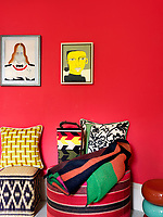 A wall of vermillion red in the living room is a colourful backdrop for contemporary art and textiles