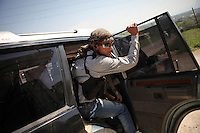 SYRIA, 04.2012, Idlib province. © Timo Vogt/EST&OST. A young member of the free syrian army jumps into a rebel jeep with a cigarette between his lips and a Kalashnikov in his hand.