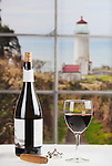 Bottle of Wine and Glass of wine on table in front of window with North Head Lighthouse in background.  White wine.