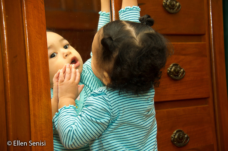 MR / Schenectady, NY. Toddler (1 year and 2 months old, African-American and Caucasian) reaches up to grasp door handle on furniture while her face is reflected in a mirror. MR: Dal4. ID: AM-HD. © Ellen B. Senisi