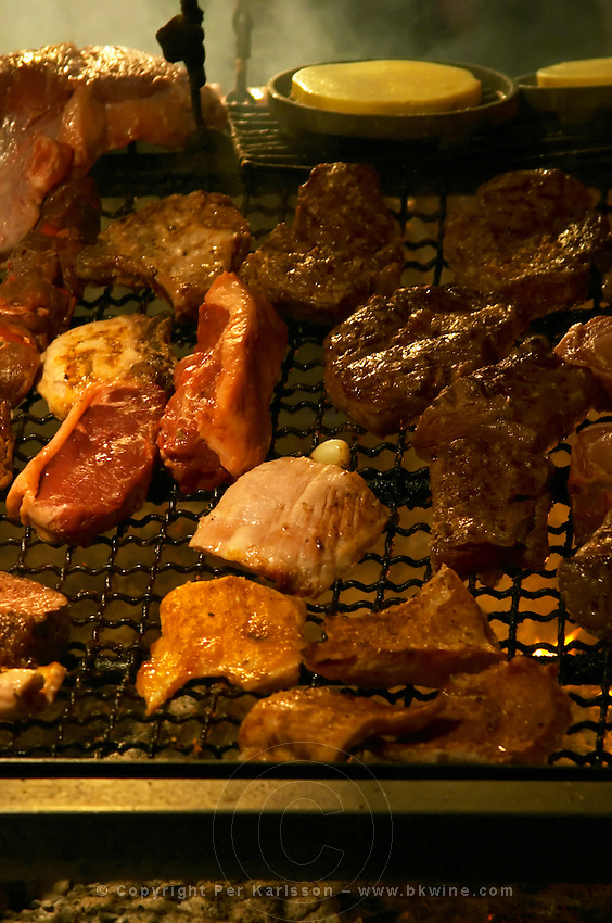 The gigantic huge charcoal grill with pieces of meat being cooked,, in the restaurant El Palenque, the sword fish swordfish, in the Mercado del Puerto, the market in the port harbour harbor where many people go and eat and shop on weekends Montevideo, Uruguay, South America
