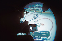 College student using a Virtual Reality experimental apparatus in a Psychology lab. The headgear is connected to a computer which follows and records eye movement vis a vis the displayed image. The hockey game is used since it's commercially available at