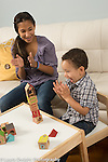 12 year old girl clapping for 2 year old toddler brother after he stacked blocks into a tower