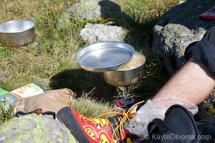 Climbe making soup on a camp stove on the trails of the Plan D'Aiguille, midway up the mountain from Chamonix to the Aiguille du Midi, Chamonix-Mont-Blanc, France