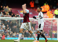 Pictured: Andy Carroll of West Ham (L) is protesting having been shown a red card by match referee Howard Webb for his header challenge against Chico Flores of Swansea. 01 February 2014<br /> Re: Barclay's Premier League, West Ham United v Swansea City FC at Boleyn Ground, London.