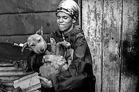 A woman carries her very ill dog to a waiting CLAW vehicle after it was determined to have billary (tick-bite fever) in the impoverished shantytown of Kliptown, South Africa.  Cora Bailey,  director of IFAW's CLAW program, which provides veterinary services to cats and dogs in some of the poorest shantytowns outside of Johannesburg, came to check on the dog after its owner called CLAW because her dog wasn't eating and asked CLAW for help. Through its mobile clinics, outreach programs and veterinary hospital, CLAW provides life-saving support to the community's animals every day. 2/21/12 Julia Cumes/IFAW