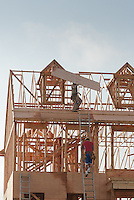 New Residential House Construction with wood framing and roof trusses and plywood against a blue sky