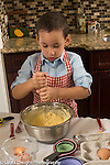 3 year old boy in kitchen at home  learning to cook baking, mixing ingredients in bowl