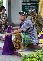 Bali, Indonesia.  Attendant Waiting to Put a Sarong around a Man Entering Uluwatu Temple Area to View the Kecak Dance.