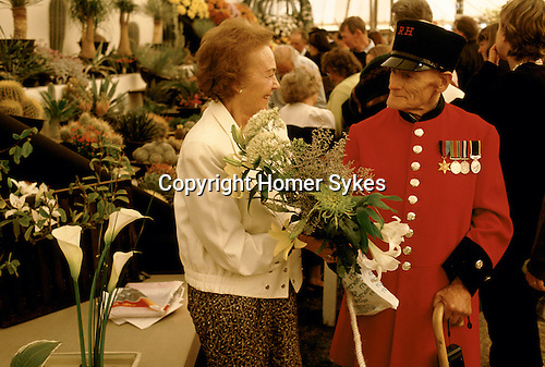 The Chelsea Flower Show. A Chelsea pensioner in his traditional formal ceremonial special occasion red uniform.  On the last day the displays are sold off very cheaply.   London 1980s.<br /> Taken for my book The English Season published by Pavilion Books 1987