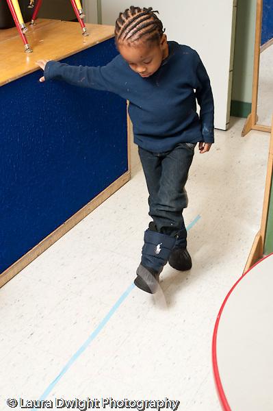 Education preschool 3-4 year olds developmental assessment boy walking along straight line on floor physical development