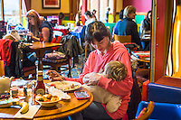 A mother eats her dinner while breastfeeding her child in the family restaurant and play area of a pub.<br /> Lancashire, England, UK<br /> <br /> Date Taken:<br /> 07-01-2015<br /> <br /> © Paul Carter / wdiip.co.uk