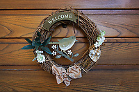 Switzerland. Canton Ticino. Sala. On the entrance door to the house of Elsy (Elsa) Hofer Ferrari Ramuz. A welcome sign with a wooden wreath, a bird and flowers.  Elsy Hofer Ferrari Ramuz is the niece of Charles-Ferdinand Ramuz (September 24, 1878 – May 23, 1947) who was a French-speaking Swiss writer. 14.11.2017 © 2017 Didier Ruef