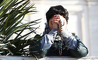 A woman prays prior to the arrival of Pope Francis to celebrate the Palm Sunday Mass in St. Peter's Square at the Vatican on March 25, 2018.<br /> UPDATE IMAGES PRESS IsabellaBonotto<br /> <br /> STRICTLY ONLY FOR EDITORIAL USE
