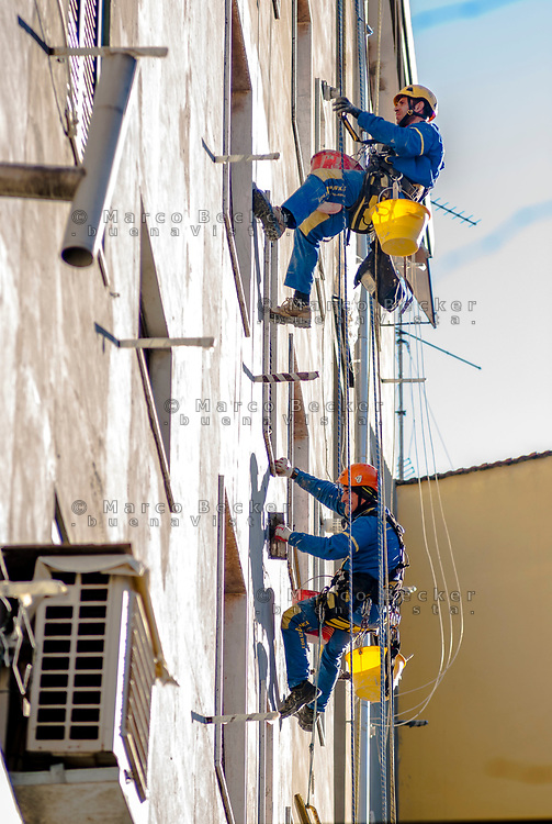 Milano, periferia nord, ristrutturazione della facciata di un palazzo. Muratori lavorano sospesi da funi --- Milan, north periphery, renovation of a building's facade. Workers suspended from ropes