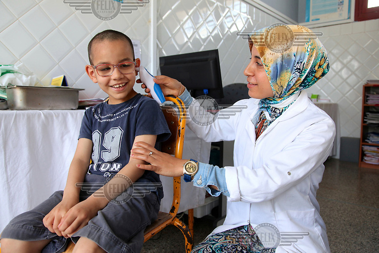 A woman takes the the temperature of a child who is resident at the 'Akkari' centre, a home for abandoned children and orphans. The centre offers a shelter to 225 boys from 5 to 18 years old.