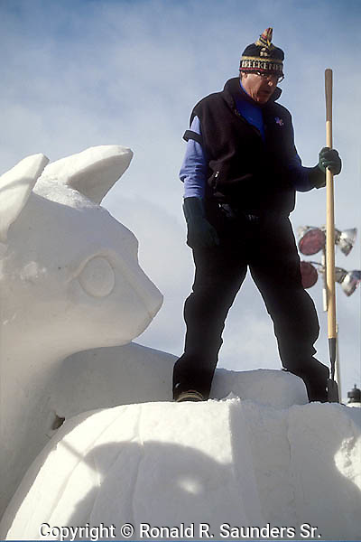 ICE SCULPTOR STANDS ALONGSIDE<br /> HIS SCULPTURE of a CAT at the ANNUAL INTERNATIONAL SNOW SCULPTURE CHAMPIONSHIPS