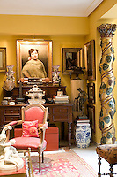 A traditional sitting room is decorated in a deep yellow and features a carved wood grape vine wrapped around a wooden pillar. Antique collectibles are displayed on a writing desk.