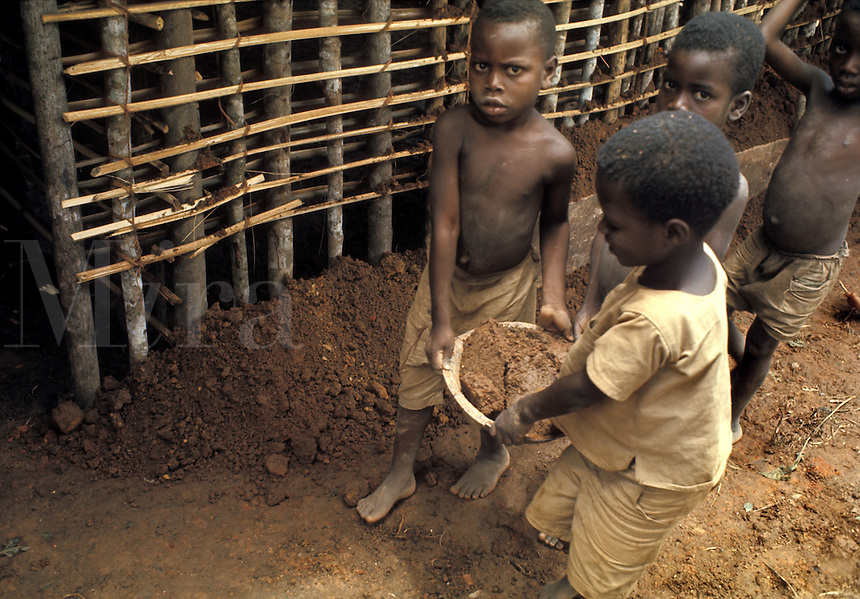 West Africa, Liberia, Kpelle tribe: children carrying mud, helping in the construction of a wattle-and-daub house.